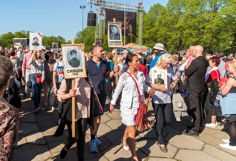 Procession of people with flags and photos their relatives in Immortal Regiment on annual Victory Day in the Victory park of Riga,. Riga, Latvia - May 9, 2018 royalty free stock images