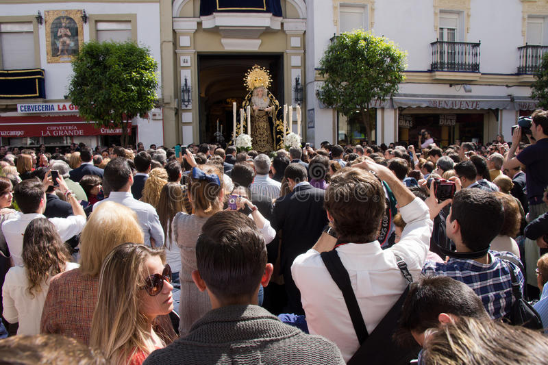 Procession in Seville. SEVILLE, SPAIN – 16 MARCH 2014: People taking pictures while Maria Auxiliadora goes into the church after the procession in the stock photography
