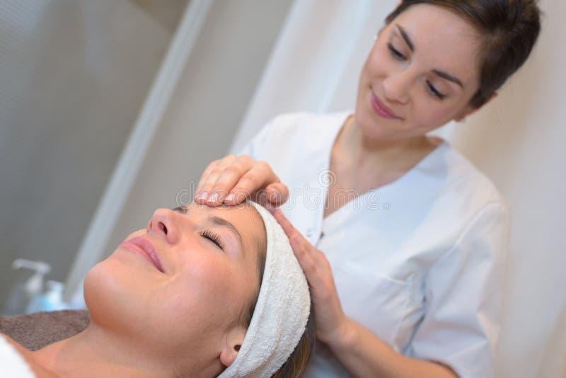 Processmassage och ansiktsbehandlingar i skönhetsalong royaltyfri foto