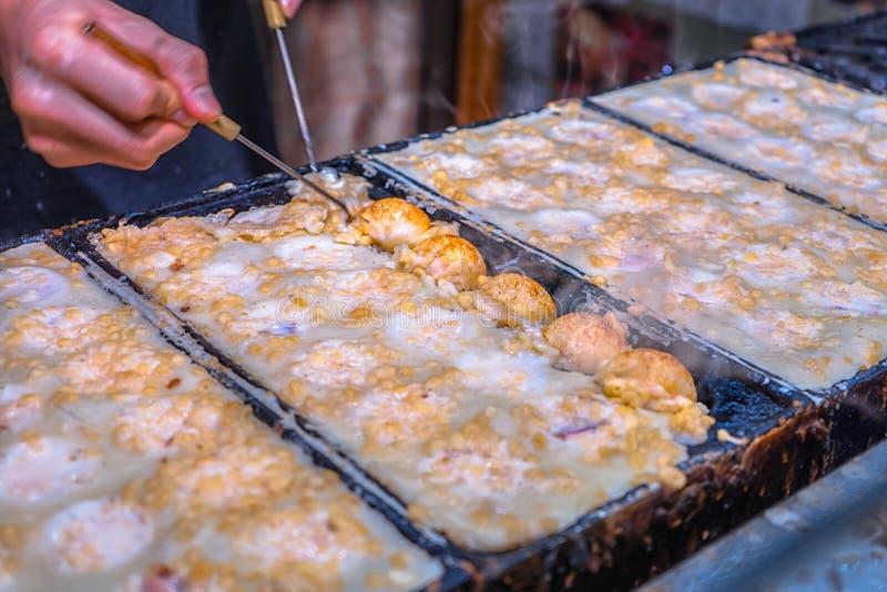 Processo a cozinhar o takoyaki em OSAKA, Japão fotos de stock royalty free