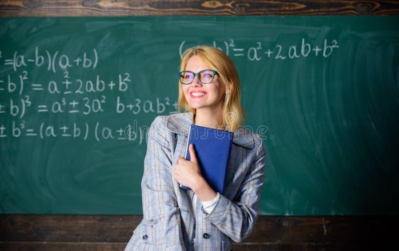 Processo da cognição na aprendizagem O professor da mulher com o livro na frente do quadro pensa sobre o trabalho Processo da cog imagem de stock