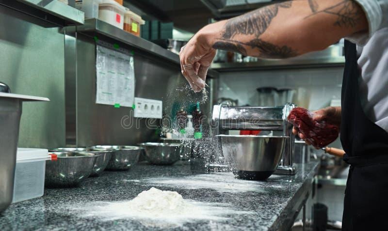 Processo de cozimento Mãos masculinas do cozinheiro chefe com as tatuagens pretas que derramam a farinha na mesa de cozinha foto de stock royalty free