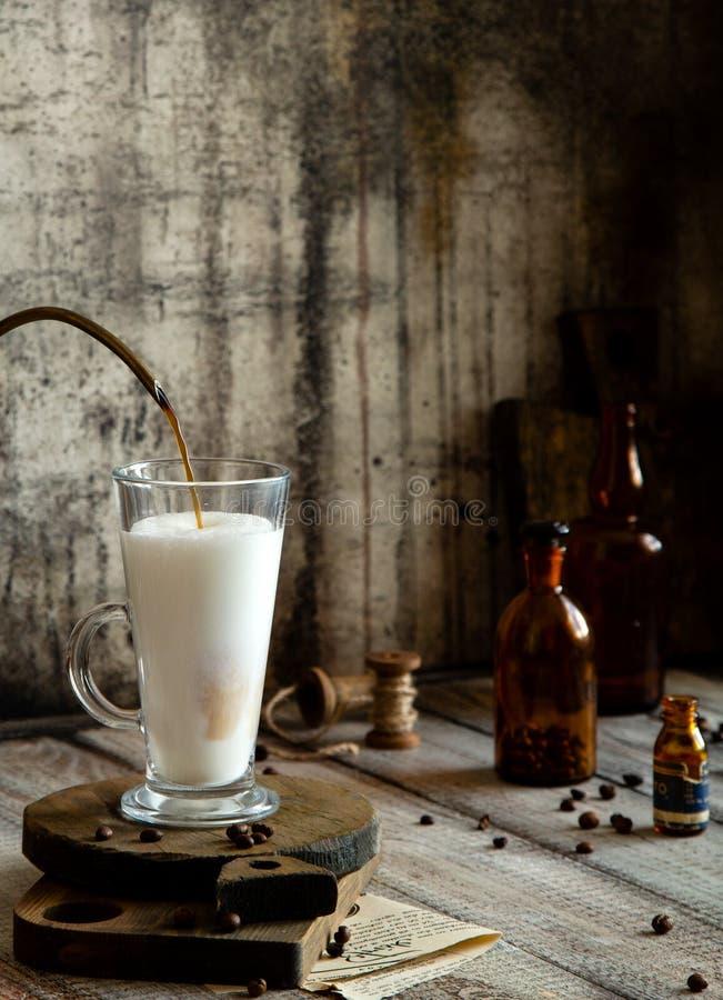 Processo de derramar o café no leite espumoso nos suportes de vidro do latte em placas de madeira na tabela rústica cinzenta fotos de stock royalty free