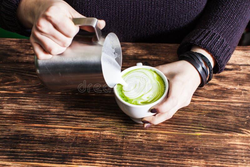 Processo de derramar o leite no copo de chá do matcha fotografia de stock royalty free