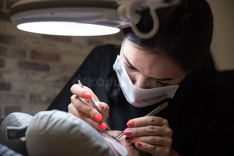 Processo de extensões da pestana no estúdio da beleza Beleza e cuidado para o senhor mesmo fotos de stock