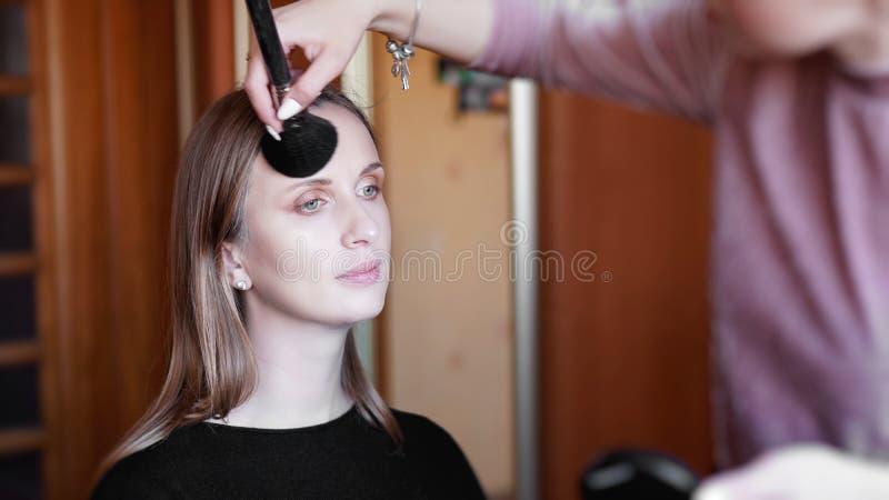 Processo de fazer a composição Artista de composição que trabalha com a escova na cara modelo imagens de stock