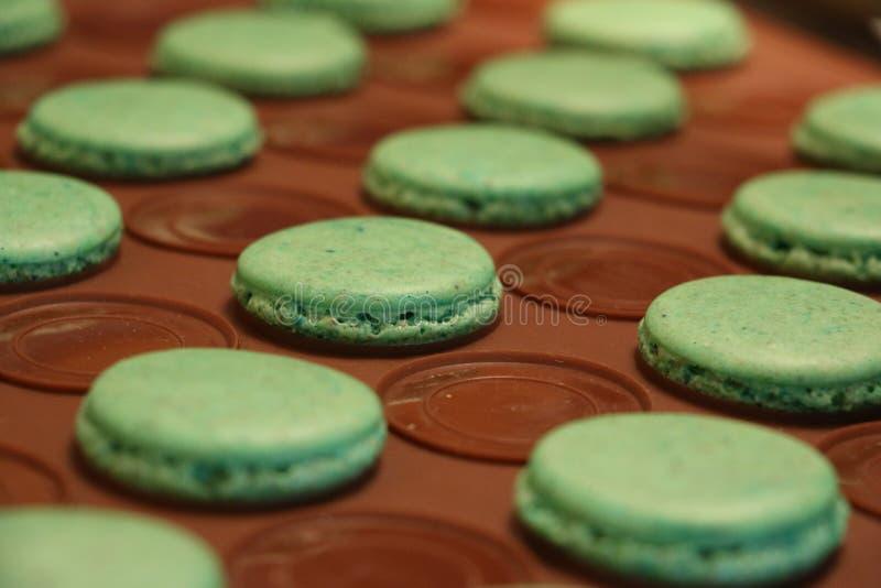 Processo de fazer macarons Apenas macarons verdes terminados na folha de cozimento do silicone imagens de stock