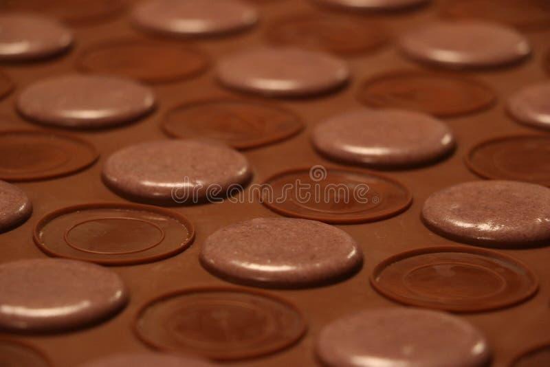Processo de fazer macarons Macarons violetas na folha de cozimento do silicone fotos de stock
