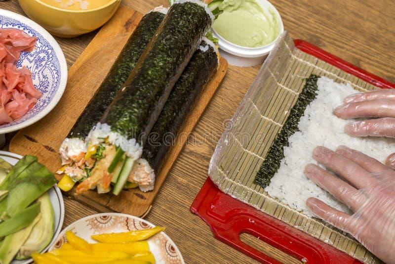 Processo de fazer o sushi e os rolos Close-up das mãos do cozinheiro chefe do homem que preparam o alimento japonês tradicional e fotografia de stock