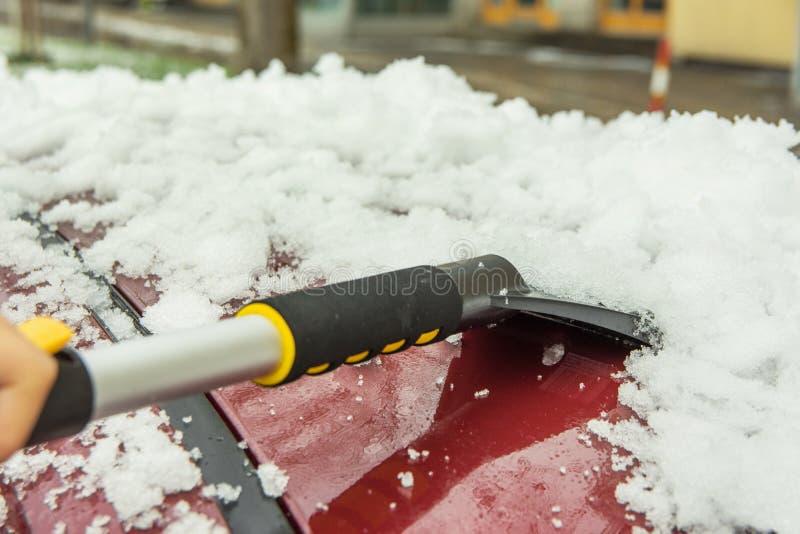 Processo de limpeza da remoção de neve após nevasca pesada com raspador de pincel formando telhado de carro no inverno Rescaldo d imagem de stock royalty free