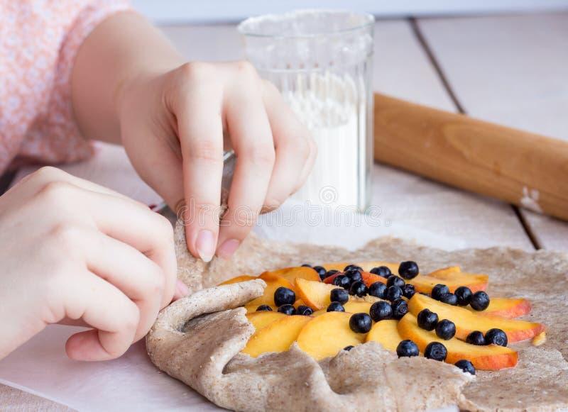 Processo de preparar biscoitos com pêssego e mirtilo, mãos imagem de stock