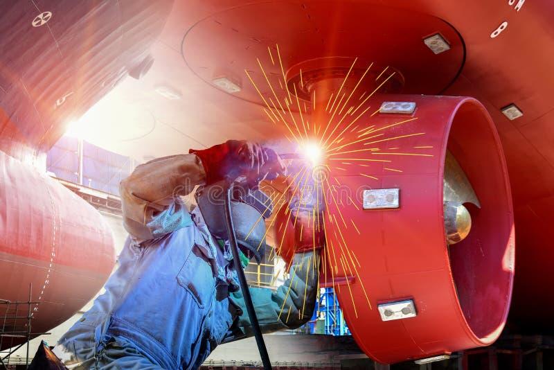 Processo de solda do trabalhador do reparo do estaleiro ou do navio com a casca de aço do metal imagens de stock royalty free
