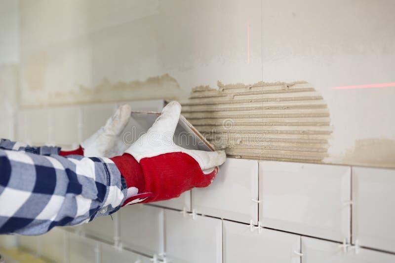 Processo de telhar as telhas na cozinha Melhoria home, com referência a foto de stock royalty free