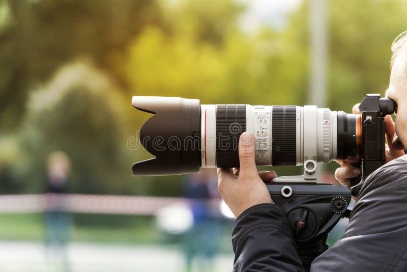 Processo de tirar fotos ao ar livre O fotógrafo profissional aproxima-se para tentar O homem atira com uma lente moderna fotos de stock royalty free