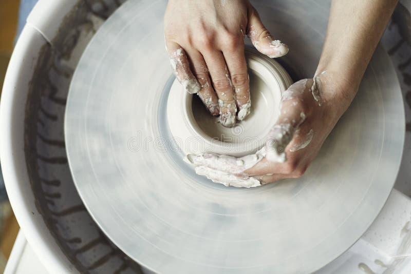 Processo de trabalho cerâmico com a roda do ` s do oleiro da argila, close-up das mãos da mulher foto de stock