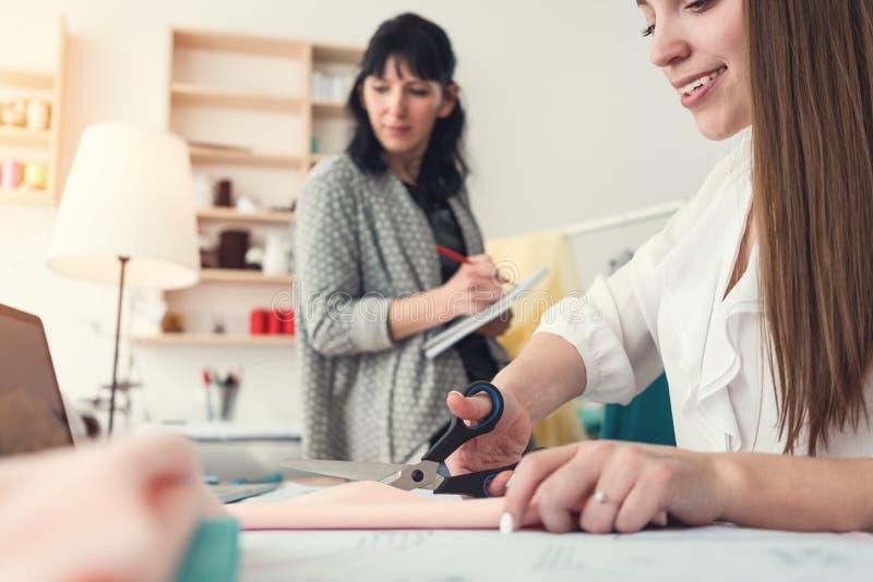 Processo de trabalho em um estúdio da costura de duas mulheres da costureira Costurar a empresa de pequeno porte A equipe de dese fotografia de stock