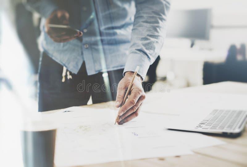 Processo de trabalho Homem de negócios que guarda as mãos do lápis, trabalhando na tabela de madeira com projeto novo Caderno gen imagem de stock