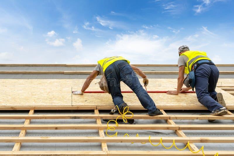 Processo della costruzione di edifici di nuovo tetto di legno sulla casa di legno di legno fotografie stock libere da diritti