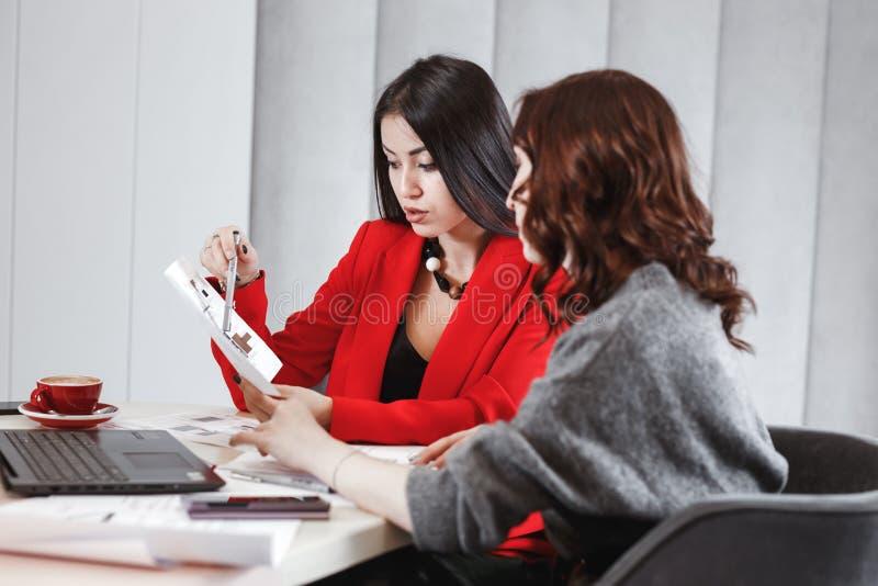 Processo della creazione di progetto Due progettisti delle ragazze stanno lavorando con il computer portatile e la documentazione fotografie stock