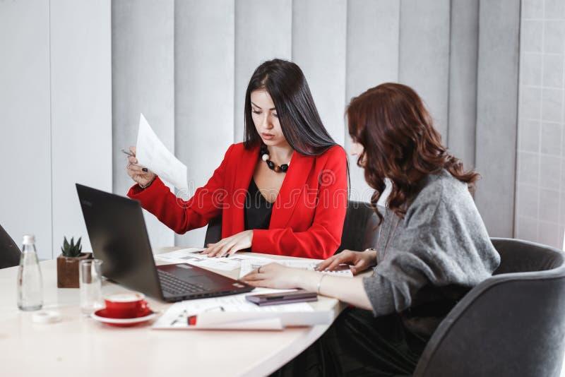 Processo della creazione di progetto Due progettisti delle ragazze stanno lavorando con il computer portatile e la documentazione fotografia stock libera da diritti
