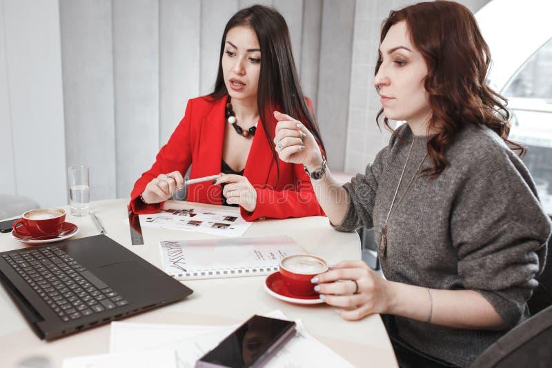 Processo della creazione di progetto Due progettisti stanno lavorando con il computer portatile e la documentazione al progetto i fotografia stock libera da diritti