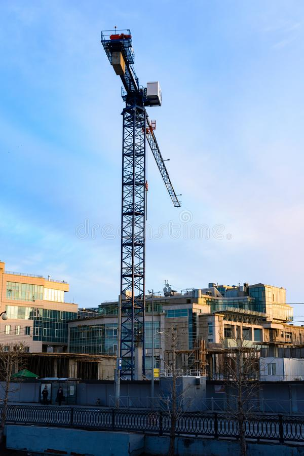 Processo di costruzione degli edifici in condominio di appartamento in un grattacielo per mezzo delle gru a torre immagine stock