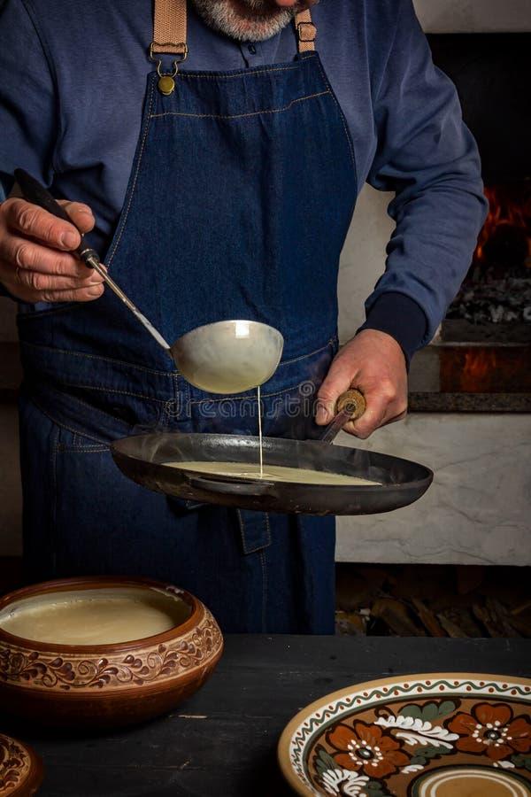 Processo di cottura dei pancake in una stufa di legno Un uomo versa la pasta dalla siviera nella pentola immagini stock libere da diritti