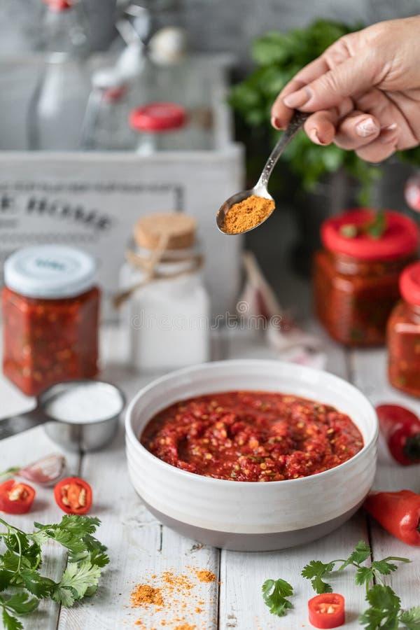 Processo di cottura della salsa piccante dei peperoni roventi Ingredienti: pepe, verdi, basilico, paprica su una tavola di legno  immagine stock libera da diritti