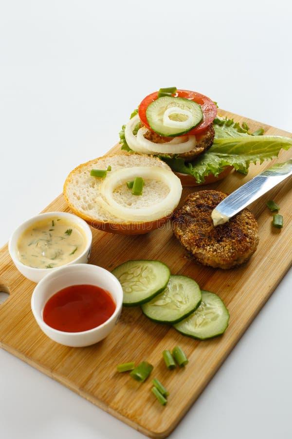 Processo di cottura di un hamburger del panino ingredienti sul tagliere di legno sulla tavola - Un ampolla sulla tavola ...