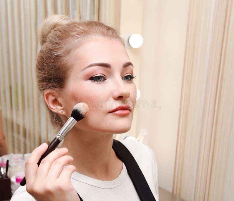 Processo di fabbricazione del trucco Bella giovane donna che applica tono per pelare Mano con la spazzola sul fronte di modello fotografie stock libere da diritti