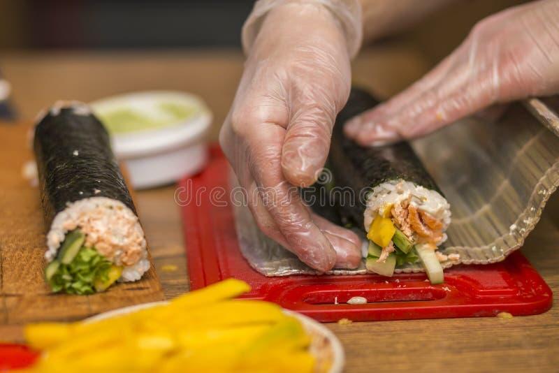 Processo di fabbricazione i sushi e dei rotoli Primo piano delle mani del cuoco unico dell'uomo che preparano alimento giapponese immagini stock