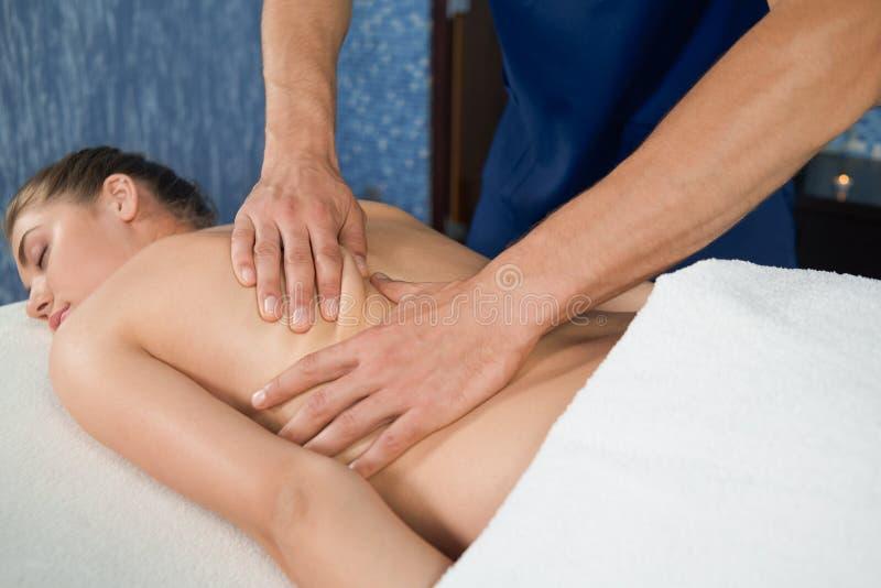 Processo di fare indietro massaggio al cliente femminile rilassato fotografie stock