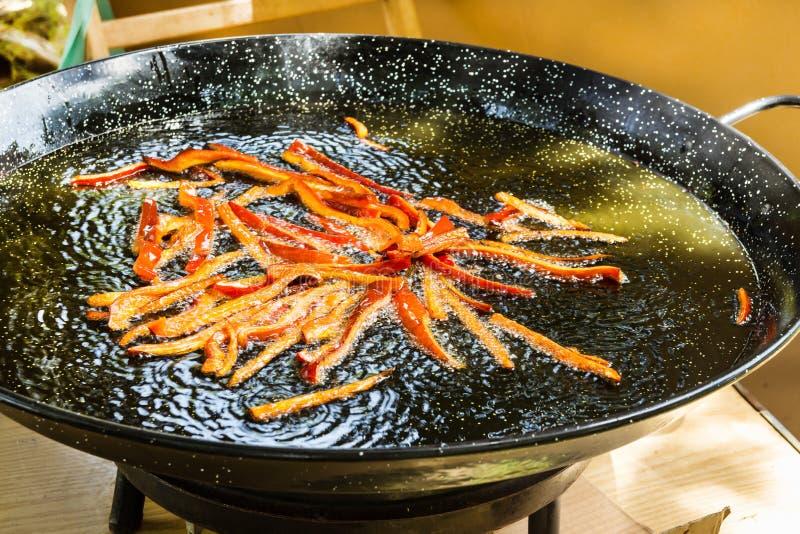 Processo di frittura nel grasso bollente delle bande del peperone dolce del capsico nel friggere olio d'oliva in pentola piana Pr fotografia stock libera da diritti