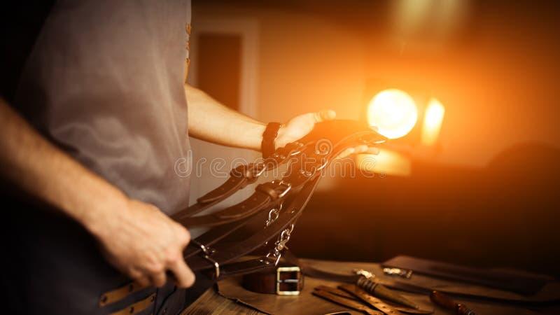 Processo di lavoro del mestiere di cuoio nell'officina Equipaggi la cinghia del ` s del fotografo della tenuta per la macchina fo fotografie stock