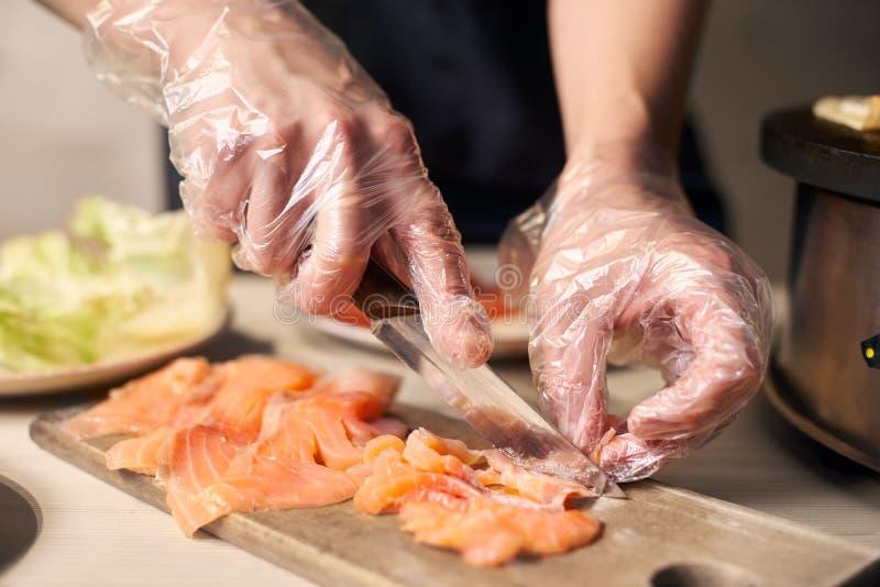 Processo di preparare le componenti per l'alimento Affettando con i pezzi del coltello di pesce sul tagliere per la cottura dell' immagine stock libera da diritti