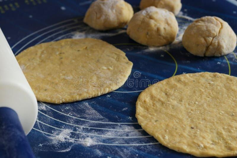 Processo di produrre pane: la pasta è srotolata sulla superficie di lavoro fotografia stock libera da diritti