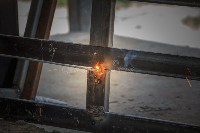 Processo di saldatura con il metallo nero del blocco e le scintille luminose in acciaio immagine stock libera da diritti