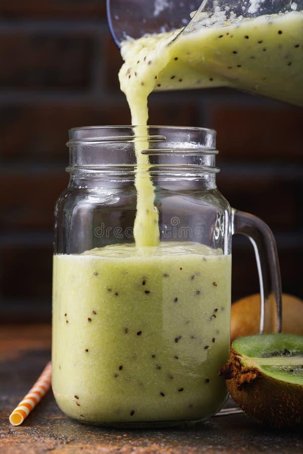 Processo di versamento dei frullati appeni preparato dal kiwi fotografia stock