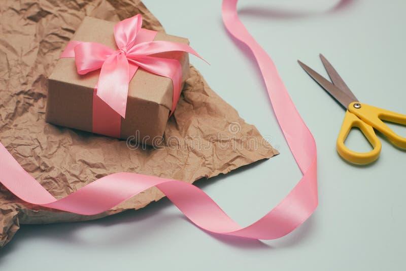 Processo do envolvimento de presentes Papel decorativo, fitas de seda, caixas de presente, tesouras Luz - fundo azul imagens de stock