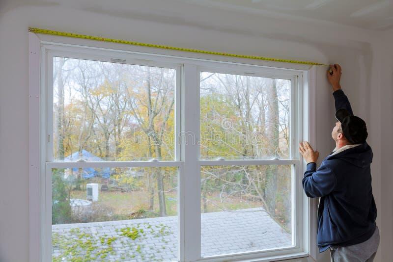 Processo per i modanature di misurazione e d'inchiodamento in costruzione sulla finestra in una nuova casa fotografia stock libera da diritti