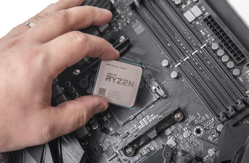Processor Ryzen 7 2700X in hand against the background of a computer motherboard. stock images