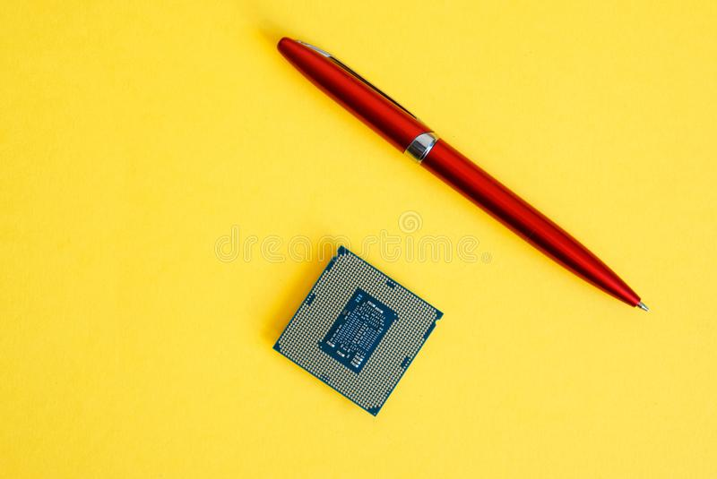 The processor for socket LGA 1151 and a pen. The processor for socket LGA 1151 and a pen on a yellow background. Computer techologies royalty free stock photo