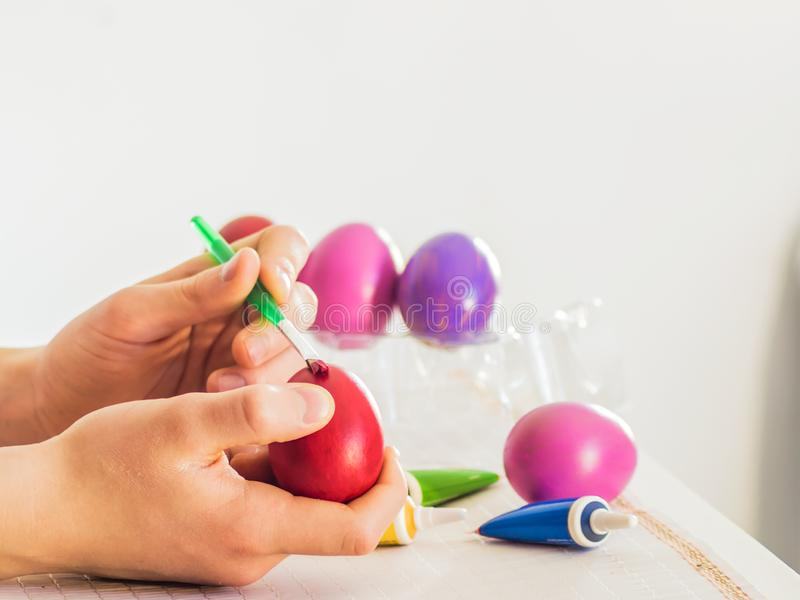 Processus de coloration d'oeuf de pâques avec une brosse des peintures acryliques, action de main sur une table blanche sur un fo illustration de vecteur