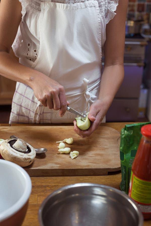 Processus de couper des légumes sur la femme âgée de conseil en bois en décor rustique de tablier blanc photo libre de droits