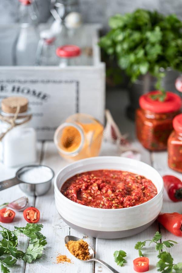 Processus de faire cuire la sauce chaude des poivrons d'un rouge ardent Ingrédients : poivre, verts, basilic, paprika sur une tab images stock