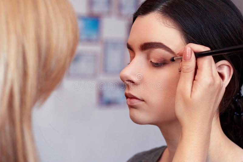 Processus de faire le maquillage Artiste de maquillage travaillant avec la brosse sur le visage modèle Portrait de jeune femme da photographie stock libre de droits