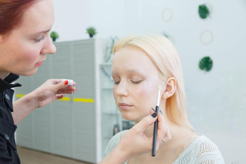 Processus de faire le maquillage Artiste de maquillage travaillant avec la brosse sur le visage mod?le images libres de droits