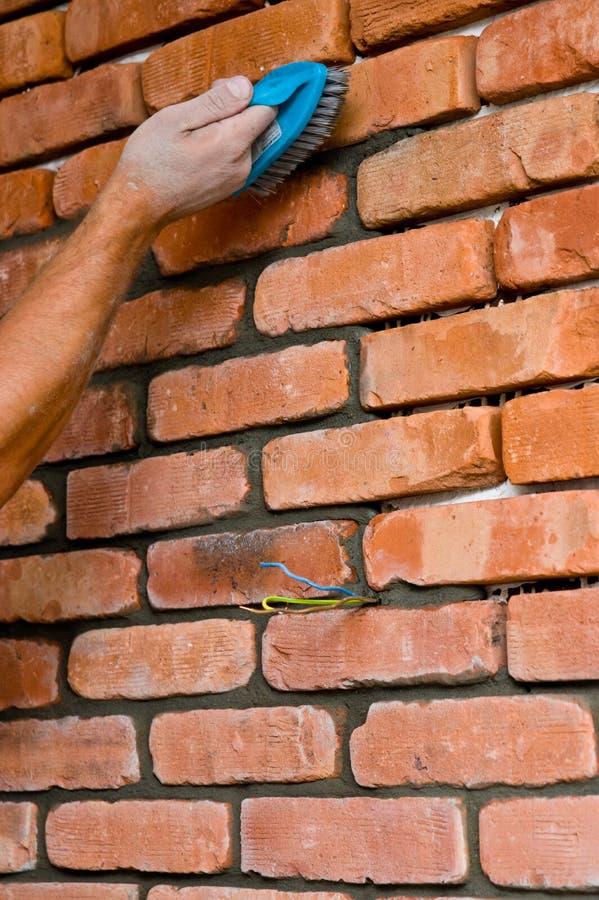 Processus de faire un mur de briques rouge, rénovation à la maison image stock