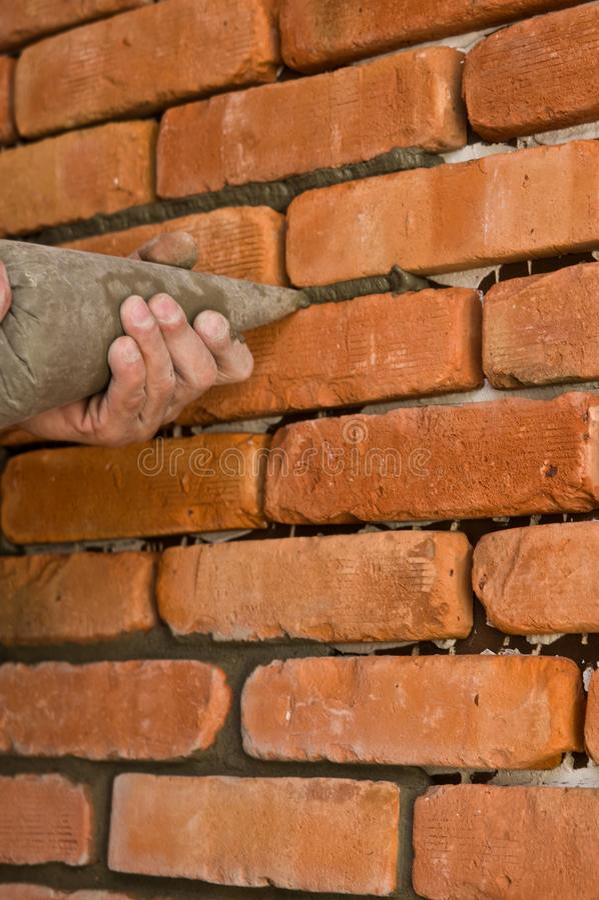 Processus de faire un mur de briques rouge, rénovation à la maison image libre de droits