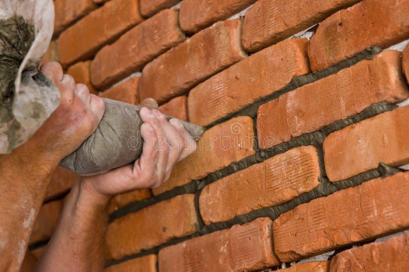 Processus de faire un mur de briques rouge, rénovation à la maison images libres de droits
